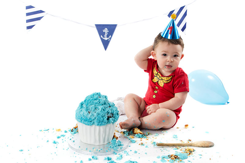 Baby and cake smash session experience. 1 year old baby behind a giant cupcake, surrounded by balloons and decorations.