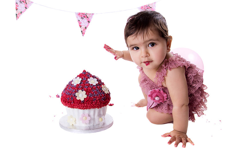 Cake smash photo shoot in bump to birthday. Baby girl reaching for a giant cupcake.