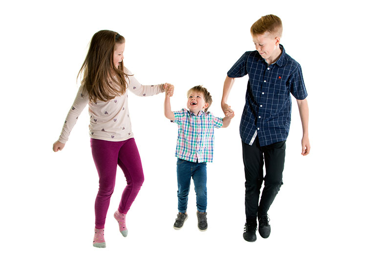 Child and family session experience. 3 siblings running in a line.