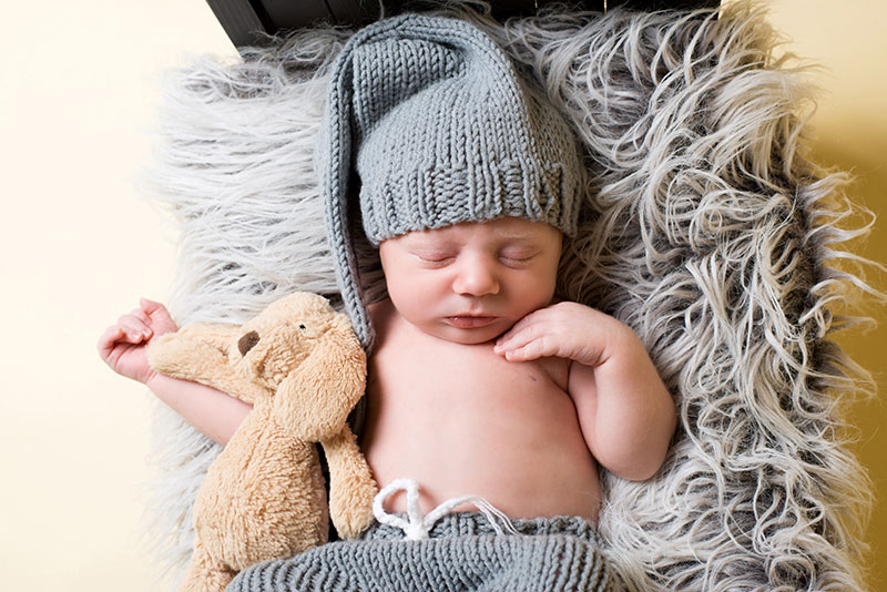 Newborn photography. Newborn baby laying on a bed prop sleeping and cuddling teddy.